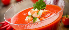 Delicious gazpacho on wooden table with fresh vegetables